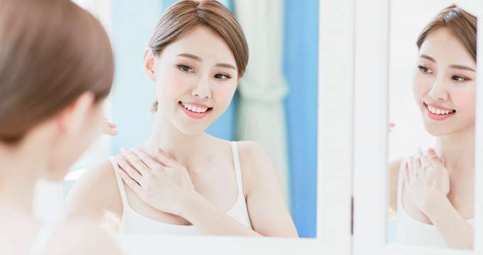 woman apply cream with neck and chest at home