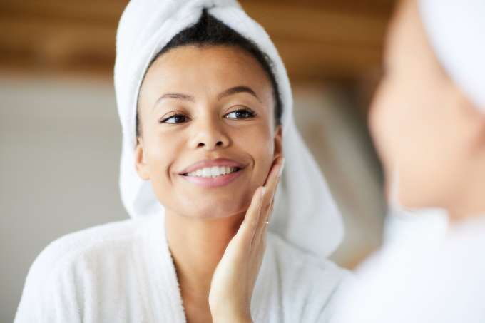 Head and shoulders portrait of  smiling woman looking in mirror during morning routine