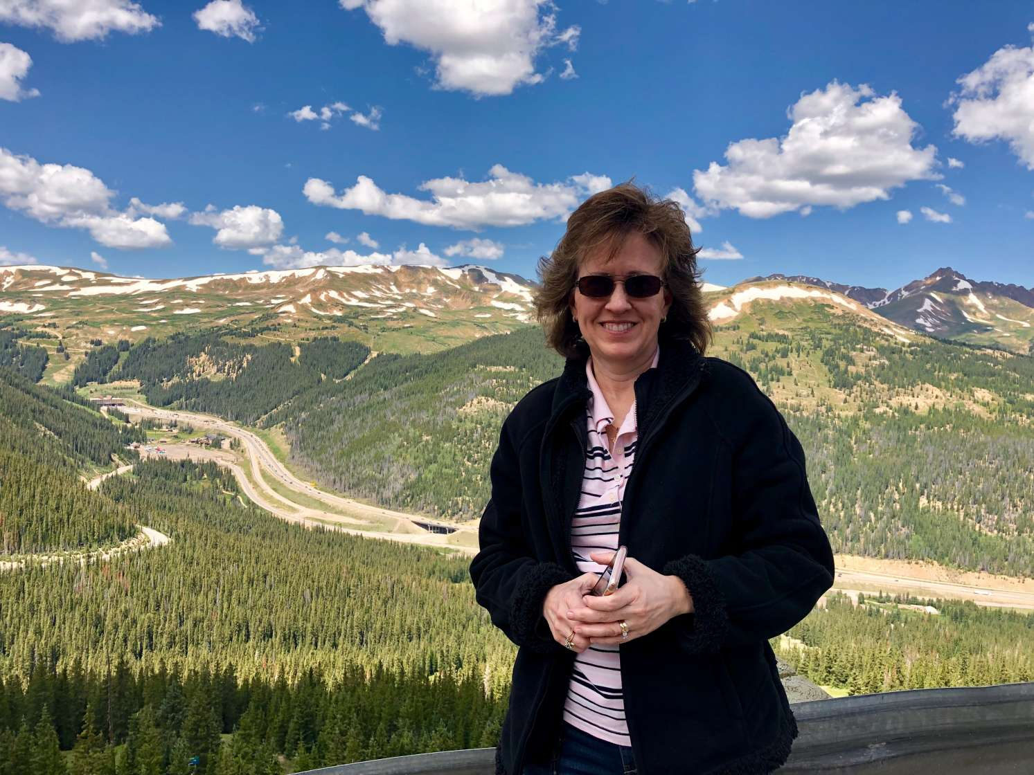 Kim Walliser is smiling at the camera with a mountain landscape in the background.